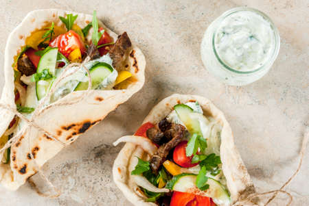 Healthy snack, lunch. Traditional Greek wrapped sandwich gyros - tortillas, bread pita with a filling of vegetables, beef meat and sauce tzatziki. On light stone table Copy space top view