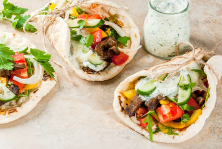 Healthy snack, lunch. Traditional Healthy snack, lunch. Traditional Greek wrapped sandwich gyros - tortillas, bread pita with a filling of vegetables, beef meat and sauce tzatziki. On light stone table Copy space wrapped sandwich gyros - tortillas, bread