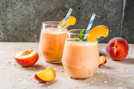 Healthy eating. Breakfast, snack. Drink smoothies from fresh peach, milk (yogurt) and oatmeal, decorated with mint leaves, with striped straws. Stock Photo