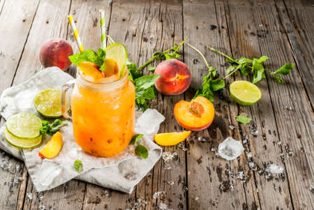 Summer drinks, cocktails. Vegan food. Peach smoothies, juice or lemonade. In a mason jar, with lime, chopped ice and mint leaves. On an old rustic wooden table with ingredients. Copy space