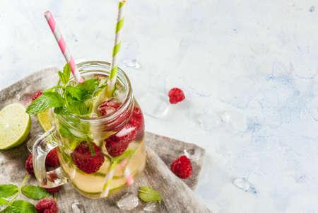 Zomerdranken, cocktails. Veganistisch eten. Geïnfundeerd detoxwater met limoen, munt en verse biologische frambozen. Op lichte betonnen tafel, ruimte kopiëren