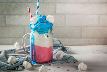 Treats for Independence Day holiday, July 4. Homemade milkshake, crazy shake with ice cream, in traditional colors - blue, red, white, decorated with stars. meringues. On white home table, copy space
