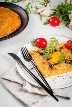 French cuisine. Breakfast, lunch, snacks. Vegan food. Traditional dish galette sarrasin. Crepes with eggs, cheese, fried mushrooms, arugula leaves and tomatoes. On white table. Copy space