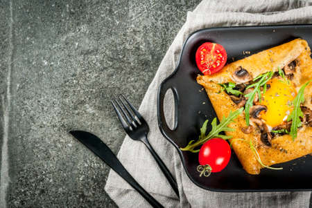 French cuisine. Breakfast, lunch, snacks. Vegan food. Traditional dish galette sarrasin. Crepes with eggs, cheese, fried mushrooms, arugula leaves and tomatoes. On black stone  table. Copy space op view