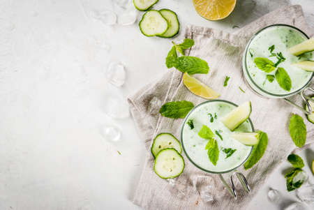 Summer food. Refreshing dishes. Cold soup of cucumber, avocado, with herbs and mint. With serving glasses, with slices of cucumber. On a white concrete table, with ingredients. Copy space top view