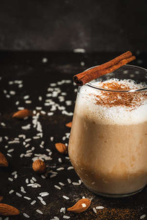 mocca: Traditional Mexican drink Horchata Latte - coffee mixed with Horchata, a cocktail of almonds, rice, vanilla and cinnamon. On a black concrete table, with ingredients. Copy space close view