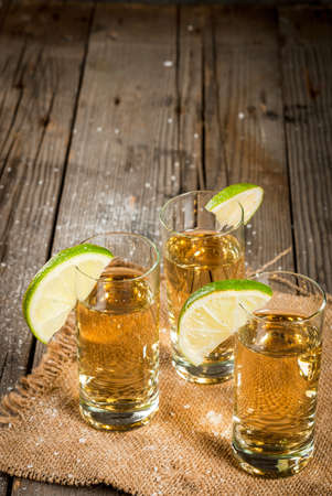 Traditional Mexican alcoholic beverage is a golden tequila. In tall glasses, with a slice of lime and salt on the background. On a wooden rustic table. Copy space