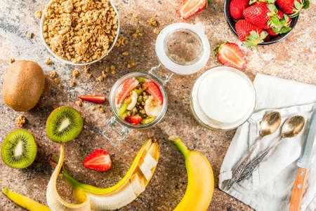 Healthy breakfast. Diet. Overnight oatmeal in a can, muesli. Yogurt with homemade granola and organic fruits - kiwi, banana, strawberry. On the stone table. With ingredients and spoons.  Top view