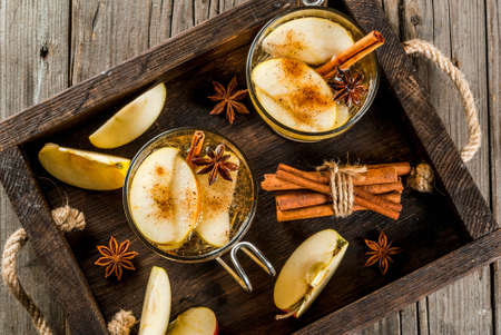 Autumn and winter drinks. Traditional home-made apple cider, cocktail of cider with aromatic spices - cinnamon and anise. On an old wooden rustic table, on a tray. Copy space top view Imagens