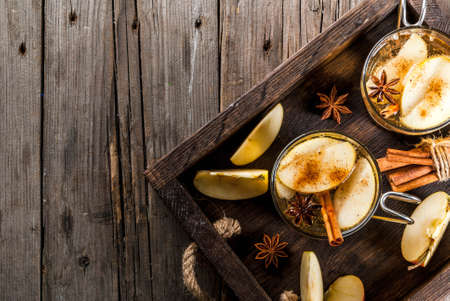 Autumn and winter drinks. Traditional home-made apple cider, cocktail of cider with aromatic spices - cinnamon and anise. On an old wooden rustic table, on a tray. Copy space top view Фото со стока