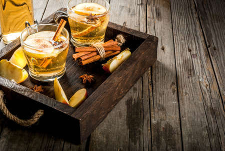 Autumn and winter drinks. Traditional home-made apple cider, cocktail of cider with aromatic spices - cinnamon and anise. On an old wooden rustic table, on a tray. Copy space