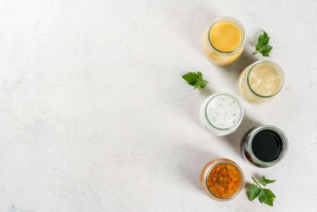 Set of dressings for salad: sauce vinaigrette, mustard, mayonnaise or ranch, balsamic or soy, basil with yogurt. Dark white concrete table. Copy space top view Banco de Imagens