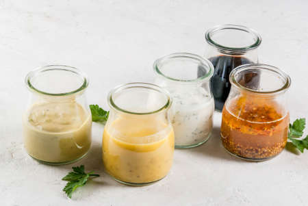 Set of dressings for salad: sauce vinaigrette, mustard, mayonnaise or ranch, balsamic or soy, basil with yogurt. Dark white concrete table. Copy space top view Фото со стока