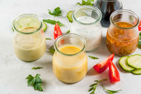 Set of dressings for salad: sauce vinaigrette, mustard, mayonnaise or ranch, balsamic or soy, basil with yogurt. Dark white concrete table, with greenery, vegetables for salad. Copy space Foto de archivo
