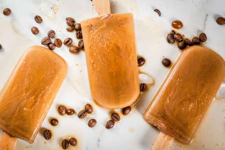 Summer desserts. Frozen drinks. Sweet popsicles made from coffee and milk. In coffee cups, On a white marble table, with coffee beans. Copy space top view