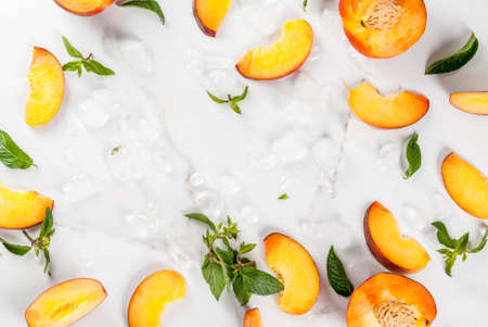 Summer refreshing cocktails, drinks. Ingredients for chilled peach tea - mint, ice and pieces of fresh yellow peach. Top view copy space