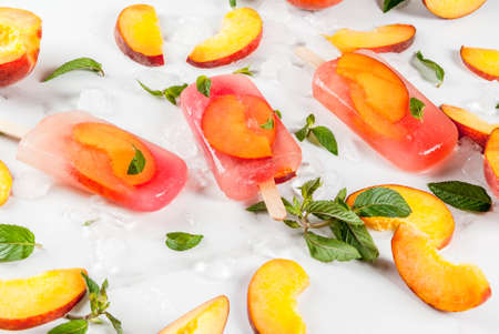 Summer desserts. Frozen drinks. Sweet fruit popsicles from frozen peach tea with mint. On a white marble table, with ingredients - peaches, mint, ice.