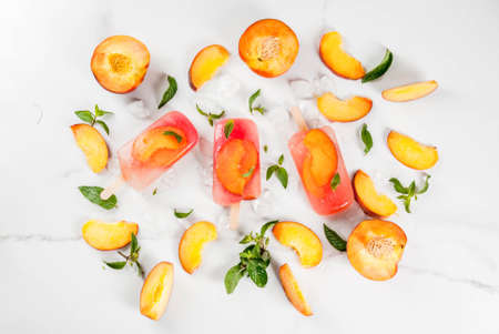 Summer desserts. Frozen drinks. Sweet fruit popsicles from frozen peach tea with mint. On a white marble table, with ingredients - peaches, mint, ice. Copy space top view Stock Photo