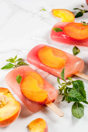 Summer desserts. Frozen drinks. Sweet fruit popsicles from frozen peach tea with mint. On a white marble table, with ingredients - peaches, mint, ice. Copy space Stock Photo