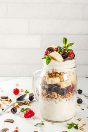 Summer fruit berry breakfast. Healthy banana split breakfast with cream cheese, raspberries, blackberries, mint, white and pink chocolate. In mason jar, marble table. Copy space Standard-Bild