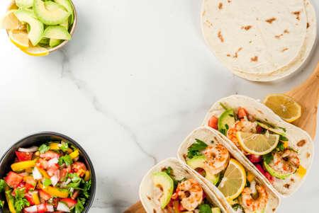 魚介類。メキシコ料理。伝統的な自家製サルサのサラダ、パセリ、レモン、アボカド、焼きエビ ポーンのトルティーヤ タコス。白い大理石の背景。 写真素材