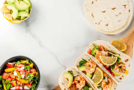 Seafood. Mexican food. Tortilla tacos with traditional homemade salsa salad, parsley, fresh lemon, avocado and grilled shrimp pawns. On a white marble background. Top view copy space 스톡 콘텐츠
