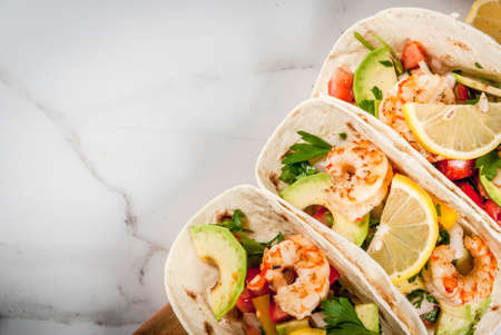 Seafood. Mexican food. Tortilla tacos with traditional homemade salsa salad, parsley, fresh lemon, avocado and grilled shrimp pawns. On a white marble background. Top view copy space Reklamní fotografie - 81459546