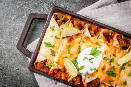 Mexican food. Cuisine of South America. Traditional dish of spicy beef enchiladas with corn, beans, tomato. On a baking tray, on a black stone background. Top view copy space Banque d'images