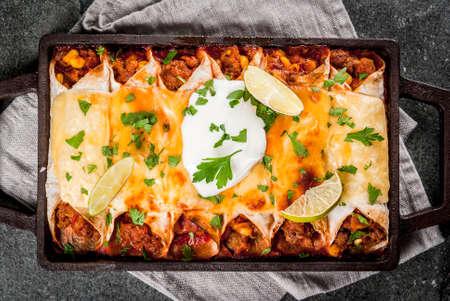 メキシコ料理。南アメリカの料理。トウモロコシ、豆、トマトのスパイシー ビーフ ・ エンチラーダの伝統的な料理。石黒地のベーキング トレイ。 写真素材