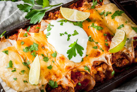 Mexican food. Cuisine of South America. Traditional dish of spicy beef enchiladas with corn, beans, tomato. On a baking tray, on old rustic wooden background. Close view