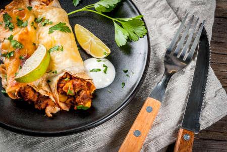 Mexican food. Cuisine of South America. Traditional dish of spicy beef enchiladas with corn, beans, tomato. On a baking tray, on old rustic wooden background. Copy space Imagens