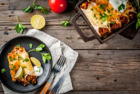 Mexican food. Cuisine of South America. Traditional dish of spicy beef enchiladas with corn, beans, tomato. On a baking tray, on old rustic wooden background. Copy space top view