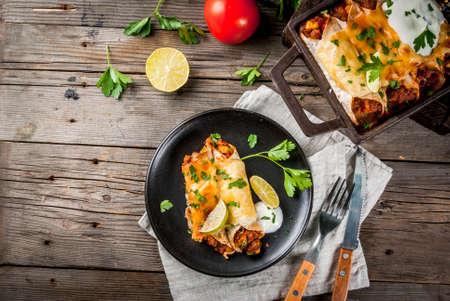 Mexicaans eten. Keuken van Zuid-Amerika. Traditionele schotel van gekruide rundvleesenchiladas met maïs, bonen, tomaat. Op een bakplaat, op oude rustieke houten achtergrond. Ruimte bovenaanzicht kopiëren