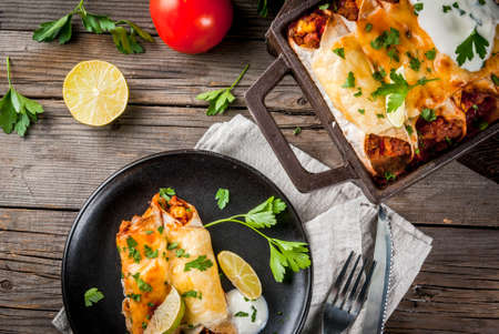 tortilla de maiz: Mexican food. Cuisine of South America. Traditional dish of spicy beef enchiladas with corn, beans, tomato. On a baking tray, on old rustic wooden background. Copy space top view