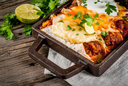 Mexican food. Cuisine of South America. Traditional dish of spicy beef enchiladas with corn, beans, tomato. On a baking tray, on old rustic wooden background. Copy space Standard-Bild