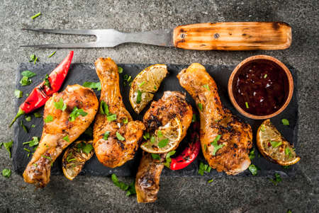 Summer food. Ideas for barbecue, grill party. Chicken legs, wings grilled, fried on fire. With hot chili pepper, lemon and bbq sauce. Dark stone table, Copy space top view