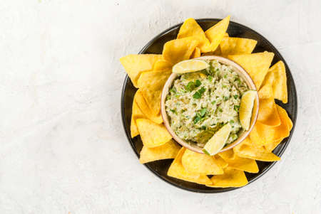 Homemade guacamole in bowl, served with tortilla nachos lime lemon and parsley, with half of avocado on white concrete table. Copy space top view Stock Photo - 81598031