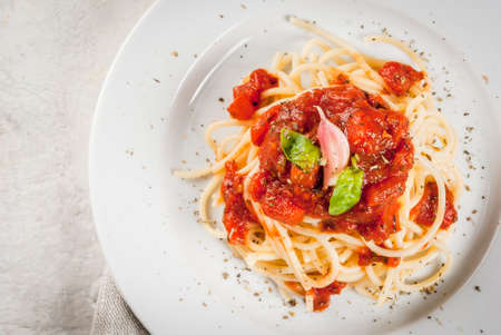 Italian cuisine. Lunch or dinner. A serving of spaghetti pasta with tomato marinara sauce and basil on a white concrete table. Close Top view copy space