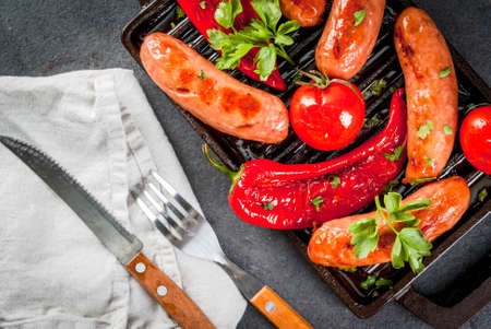 Barbecue. Home hotdogs. Grilled vegetables. sausages, tomatoes and peppers on a grilled baking sheet, cooked. With spices and herbs. With buns bread. On black stone table. Copy space