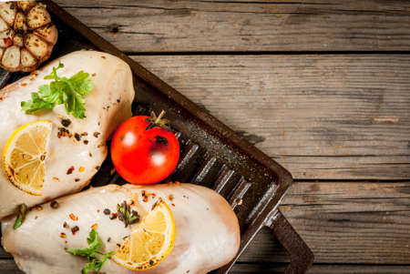 Grilled chicken breast during frying. With lemon, greens and garlic on the brazier for grilling. On old rustic wooden table. Top view copy space Stock Photo