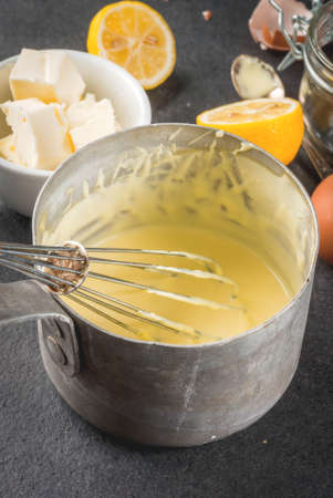 Traditional basic sauces. French cuisine. Hollandaise sauce in a metal saucepan, with ingredients for cooking - eggs, butter, lemons. On a black stone table. Copy space top view Stock Photo - 81598039