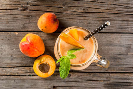 Homemade organic smoothie from yogurt and apricot. In Mason Jar, on a rustic old wooden table, with apricots and mint leaves. Copy space top view