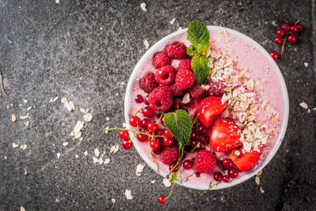Ideas for healthy summer breakfast. Smoothies in bowls wth red (strawberry raspberry currant), blue (blueberry blackberries) berry With oatmeal, fresh berries. Dark stone table. Top view copy space