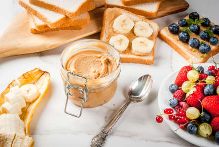 Traditional American and European summer breakfast: sandwiches of toast with peanut butter, berry, fruit apple, peach, blueberry, blueberry, strawberry, banana. White marble table. copy space