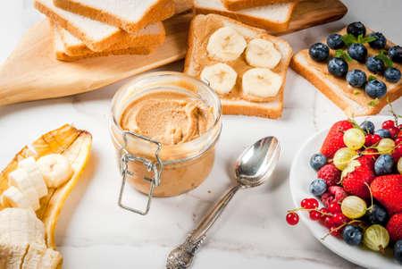Traditionelles amerikanisches und europäisches Sommerfrühstück: Sandwiches von Toast mit Erdnussbutter, Beere, Obstapfel, Pfirsich, Heidelbeere, Heidelbeere, Erdbeere, Banane. Weißer Marmortisch. kopieren Sie Platz