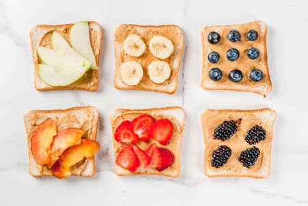 Desayuno de verano típico americano y europeo: sándwiches de pan tostado con mantequilla de cacahuate, bayas, manzanas de fruta, melocotón, arándano, arándano, fresa, plátano. Mesa de mármol blanco. Espacio de copia vista superior Foto de archivo - 81999885