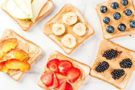 banana bread: Traditional American and European summer breakfast: sandwiches of toast with peanut butter, berry, fruit apple, peach, blueberry, blueberry, strawberry, banana. White marble table. copy space top view