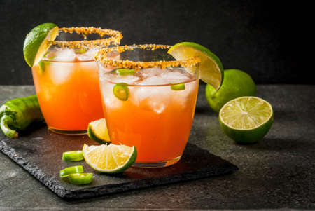 Alcohol. Traditional Mexican South American cocktail. Spicy michelada with hot jalapeno peppers and lime. On a dark stone table. Copy space 스톡 콘텐츠