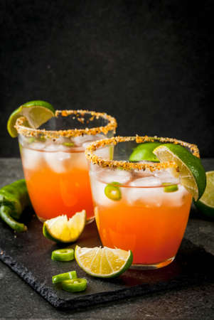 Alcohol. Traditional Mexican South American cocktail. Spicy michelada with hot jalapeno peppers and lime. On a dark stone table. Copy space Stockfoto