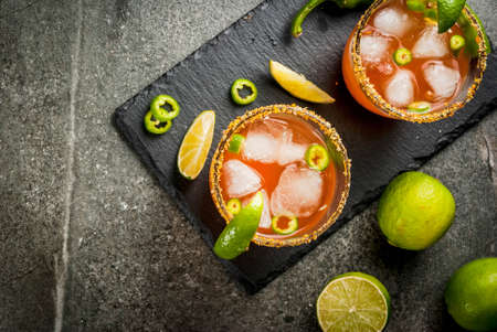 Alcohol. Traditional Mexican South American cocktail. Spicy michelada with hot jalapeno peppers and lime. On a dark stone table. Copy space top view